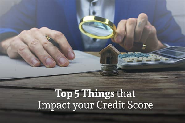 "A man reads a document through a magnifying glass, a calculator and tiny home model sit before him and below are the words ""Top 5 Things that Impact your Credit Score"""
