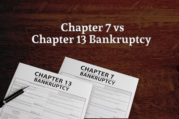 "A form for Chapter 7 bankruptcy and one for Chapter 13 bankruptcy sit along with a pen atop a table under the words ""Chapter 7 vs Chapter 13 Bankruptcy"""
