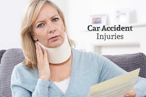 "A woman with a neck brace holds a piece of paper beside the words ""Car Accident Injuries"""