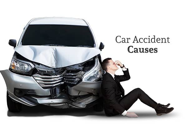 "A man sits next to his wrecked car looking distressed beneath the words ""Car Accident Causes"""