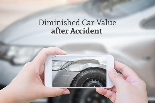 Diminished Car Value after Accident with a car in the background that a person is taking a picture of the damage on with their phone