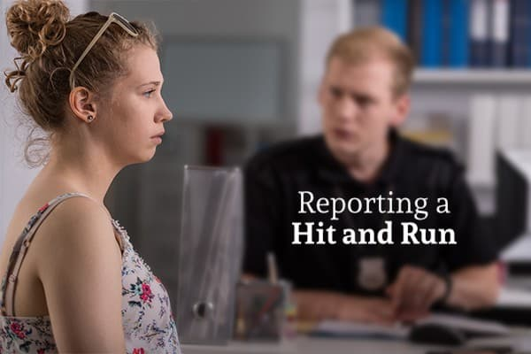 A woman looking shocked and worried, sitting on the other side of a desk from a man who is helping her file a report, with the words reporting a hit and run